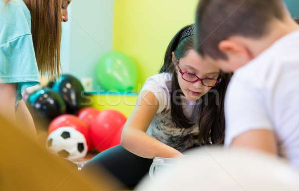 Kindergarten female teacher coordinating children during group activity Stock photo © Kzenon
