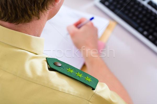 Police Officer working on desk in station Stock photo © Kzenon