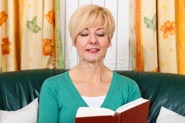 Mujer madura lectura libro casa salón mujer Foto stock © Kzenon