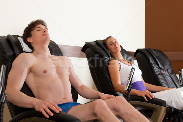 Couple on massage chair in gym Stock photo © Kzenon