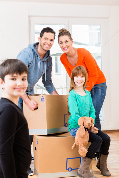 Family with moving boxes in new home or house Stock photo © Kzenon