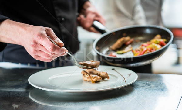 Chef finishing food on plate in restaurant kitchen Stock photo © Kzenon