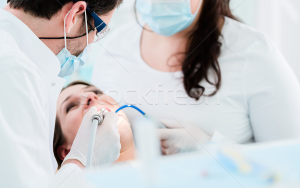Dentist treating woman patient with drill Stock photo © Kzenon