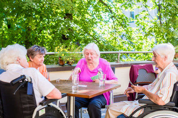 Group of seniors playing board game on terrace of retirement hom Stock photo © Kzenon