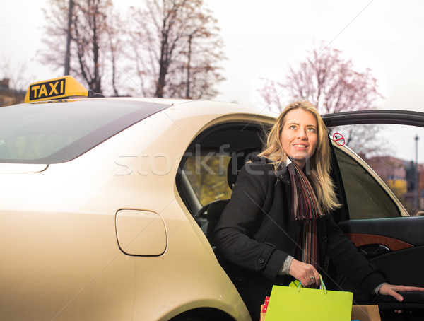 Young woman gets out of taxi with shopping bags Stock photo © Kzenon