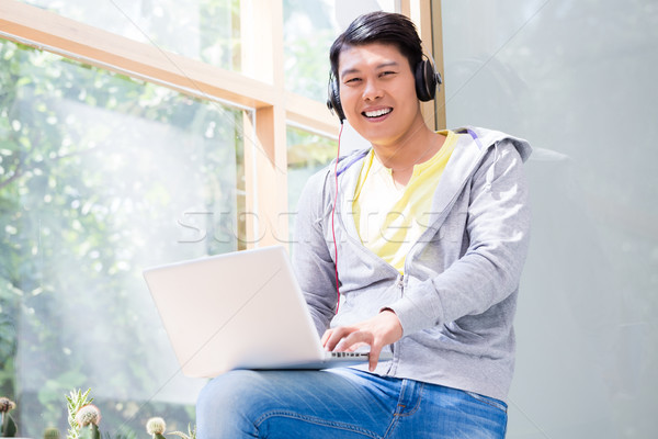 Chinese young man wearing casual clothes while using a laptop Stock photo © Kzenon