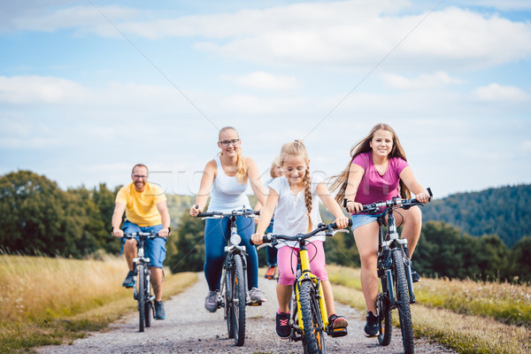 Family riding their bicycles on afternoon in the countryside Stock photo © Kzenon