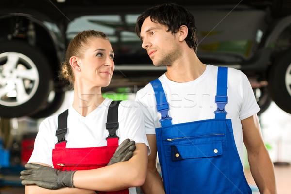 Car mechanics male and female in front of auto Stock photo © Kzenon