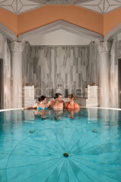 Three friends in swimming pool or thermal bath Stock photo © Kzenon