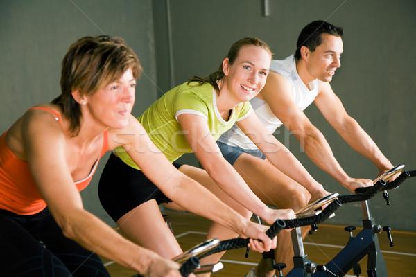 Uygunluk bisiklete binme üç kişi spor salonu kulüp renkli Stok fotoğraf © Kzenon