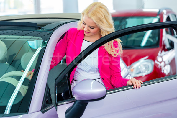 Woman choosing car for buying in dealership  Stock photo © Kzenon