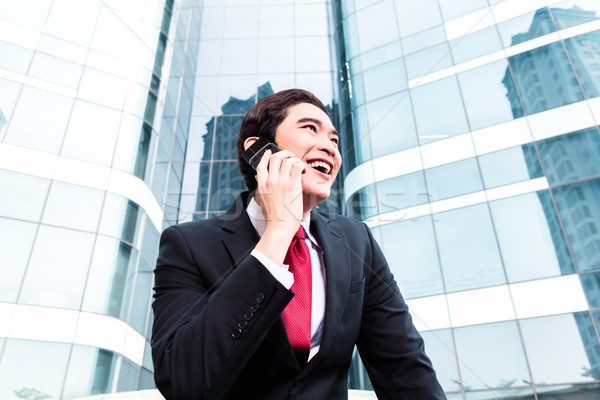 Asian business man talking outside to mobile phone Stock photo © Kzenon
