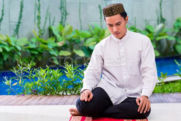 Asian Muslim man praying on carpet Stock photo © Kzenon
