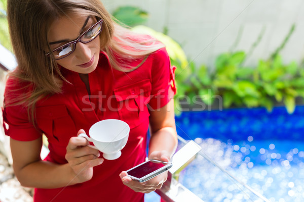 Woman drinking coffee checking Mails on phone Stock photo © Kzenon