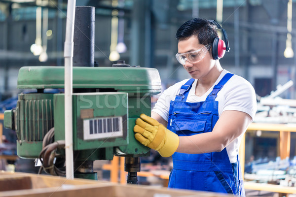 Asian worker in factory on drilling machine Stock photo © Kzenon