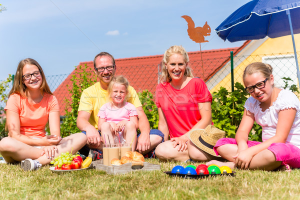 Family having picnic in garden front of their home Stock photo © Kzenon