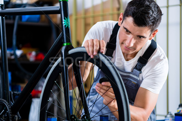 Mechanic repairing bicycle in his workshop Stock photo © Kzenon