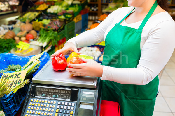 Saleswoman weighting vegetables on scale in grocer Stock photo © Kzenon