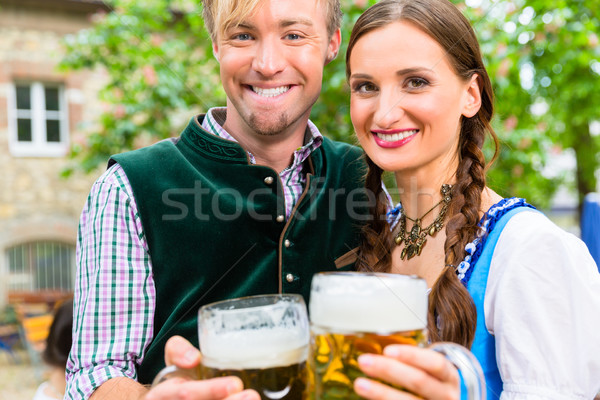 Couple wearing Tracht posing with glasses in beer garden Stock photo © Kzenon