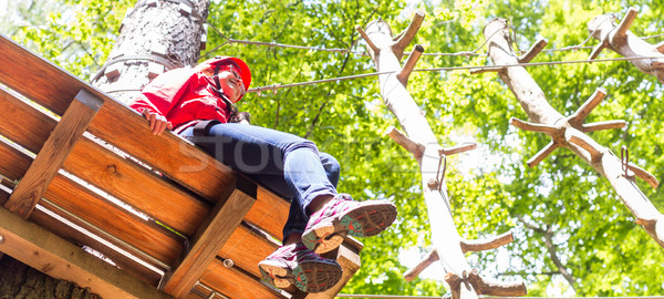 Girl sitting on platform in high rope course resting Stock photo © Kzenon