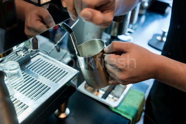 Hand of a barista holding a stainless mug while using a modern c Stock photo © Kzenon