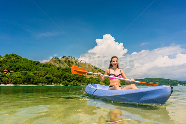 Young woman paddling during vacation in an idyllic travel destin Stock photo © Kzenon