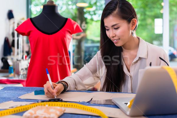 Asian fashion designer preparing drafts for cut-outs Stock photo © Kzenon