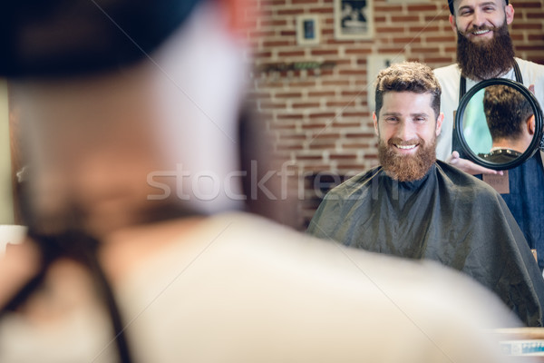 Young man smiling while looking at his new trendy haircut in the Stock photo © Kzenon