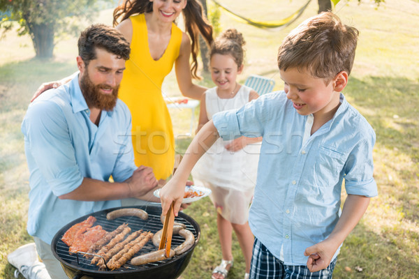 Father and son preparing meat on charcoal barbecue grill during picnic Stock photo © Kzenon