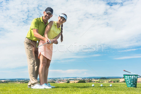 Young woman practicing the correct move during golf class with a skilled player Stock photo © Kzenon
