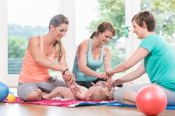 Young women practicing how to wrap children in mother-child less Stock photo © Kzenon