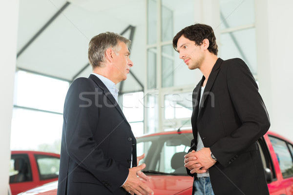 Mature dealer and young man with auto in car dealership Stock photo © Kzenon