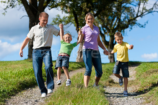 Family outdoors is running on a dirt path Stock photo © Kzenon