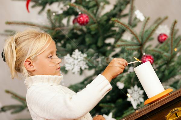 Stock photo: Child lighting Christmas candles