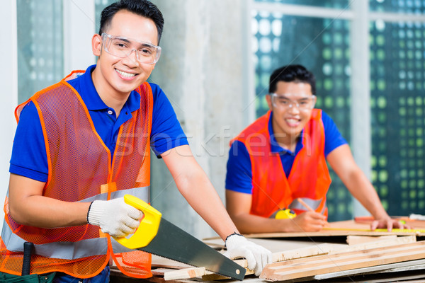 Builder sawing a wood board of building or construction site  Stock photo © Kzenon