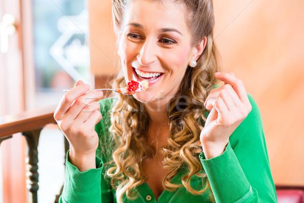 Woman eating cake at pastry shop Stock photo © Kzenon