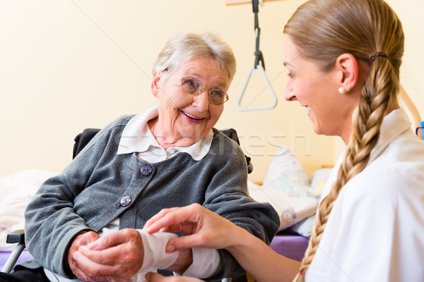 Nurse taking care of senior woman in retirement home Stock photo © Kzenon