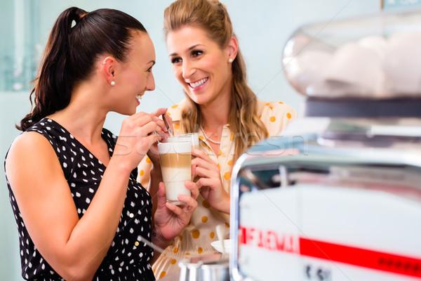 Girl friends drinking latte macchiato in coffee bar Stock photo © Kzenon