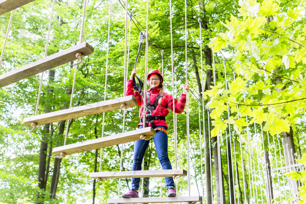 Kid walking on rope bridge in climbing course Stock photo © Kzenon