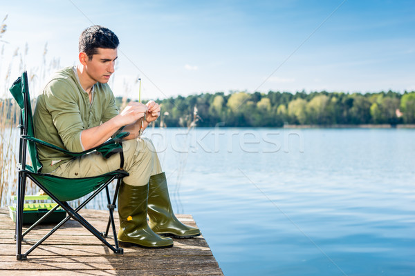 Man fishing at lake fixing lure at angling rod Stock photo © Kzenon