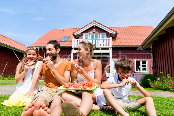 Family sitting in grass front of home eating water melon Stock photo © Kzenon