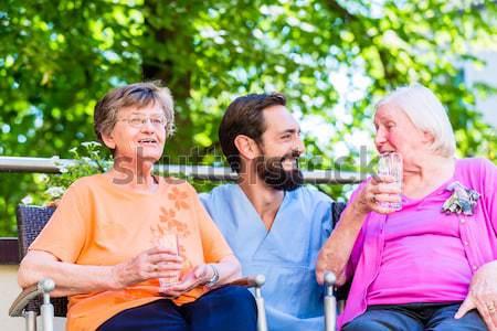 Senior women in rest home with geriatric nurse Stock photo © Kzenon