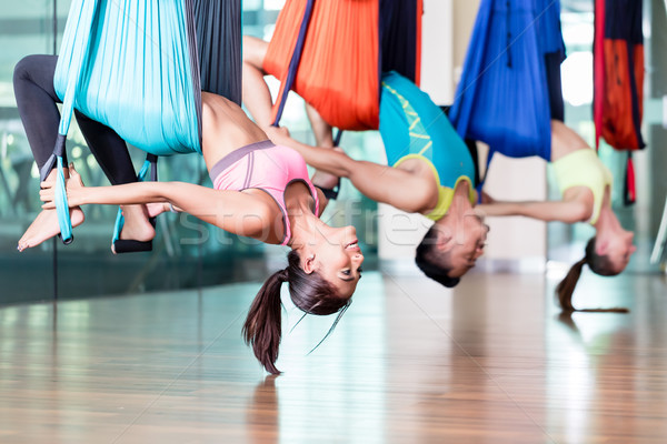 Fit young woman practicing aerial yoga during group class in a m Stock photo © Kzenon