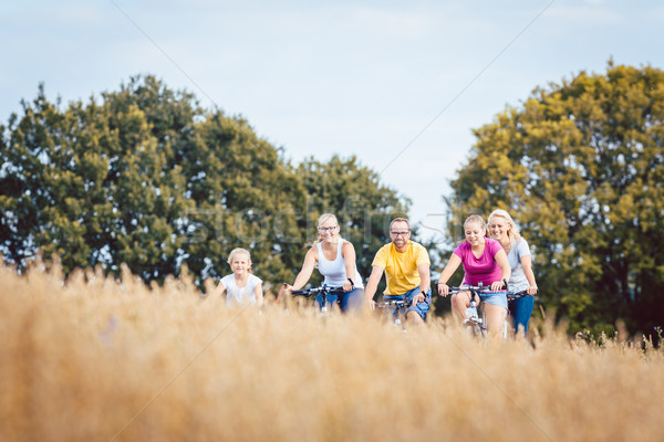 Stock photo: Family riding their bikes shot above a grain field