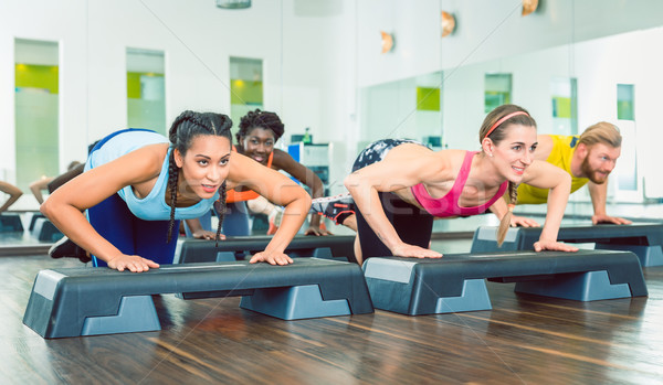 Determined women exercising push-ups on aerobic stepper platform Stock photo © Kzenon