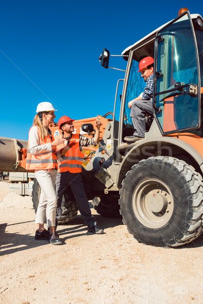 Civil engineer and worker discussion on road construction site Stock photo © Kzenon