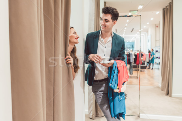 Man in fashion store waiting for his woman to appear from the fitting room Stock photo © Kzenon