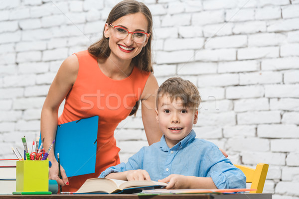 Teacher and pupil doing task together Stock photo © Kzenon