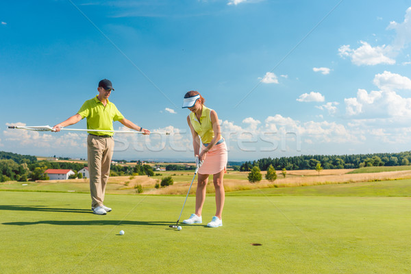 Full length of a woman playing professional golf with her male match partner Stock photo © Kzenon