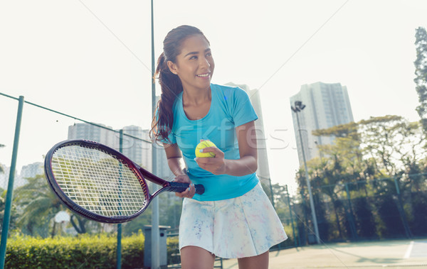 Professional female player smiling while serving during tennis match Stock photo © Kzenon